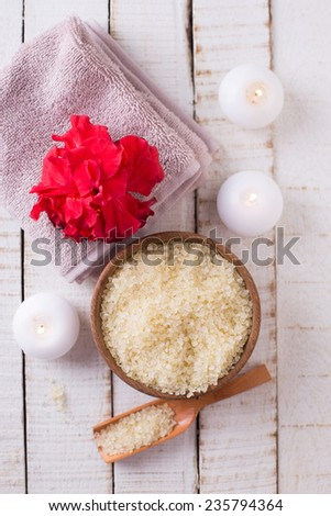 Spa setting with sea salt, flower, towel and candles on white painted wooden boards. Selective focus.