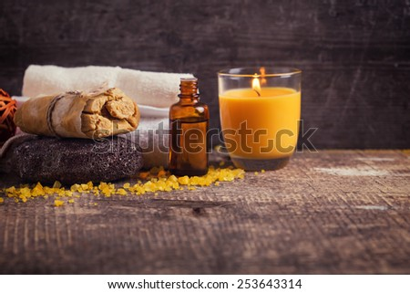 Spa setting with soap, towels, candle, oil,  pumice on aged wooden background. Selective focus is on soap. - stock photo