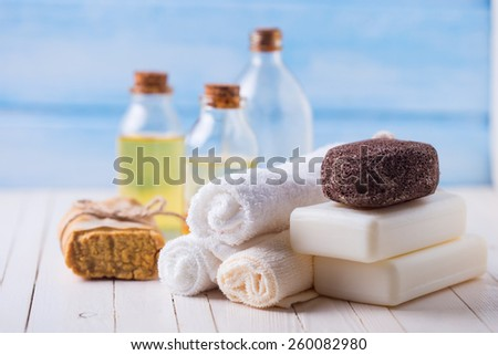 Spa setting with soap, towels, pumice and aroma oil on  painted wooden boards. Selective focus is on towels. - stock photo