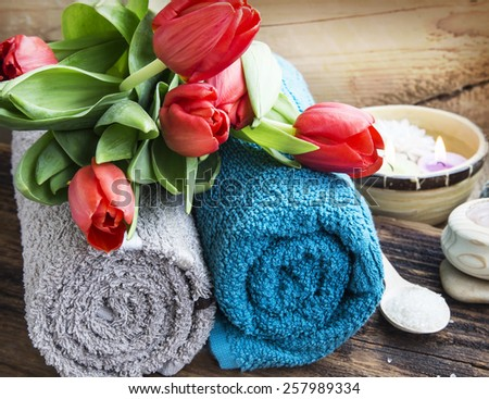 Spa Setting with Soft Cotton Towels and Red Tulips on Wooden Background - stock photo