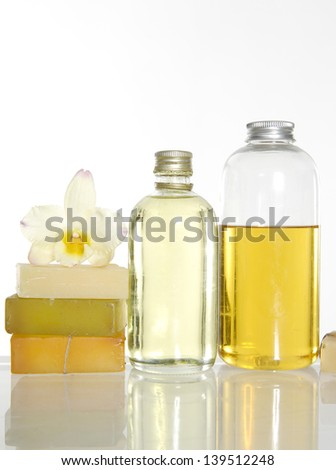 spa setting with stacked soap and massage oil with orchid