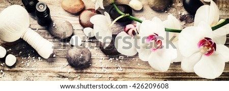 Spa setting with white orchid, herbal massage ball and essential oil. Wellness concept - stock photo