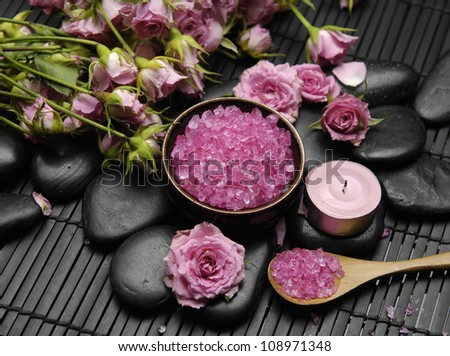spa settings � branch pink rose with salt in bowl and candle on mat - stock photo
