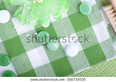 spa settings, green towel with white and green spa stone, hairbrush - stock photo