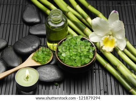 Spa Settings (zen stones, massage oil, bamboo grove , orchid, sea salt in bowl) - stock photo