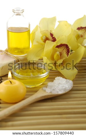 Spa sitting with yellow orchid, salt in spoon, candle, oil - stock photo