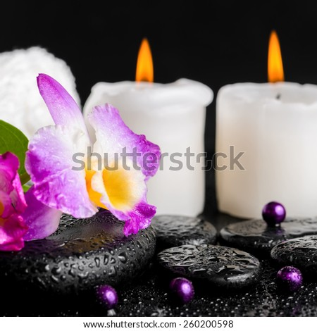 spa still life of purple orchid dendrobium, leaf with dew, towels, white candles and pearl beads  on black zen stones, closeup   - stock photo