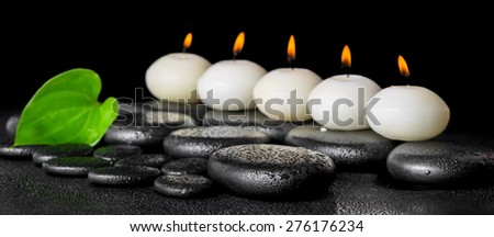 spa still life of row white candles and green leaf on black zen stones background with dew, panorama - stock photo