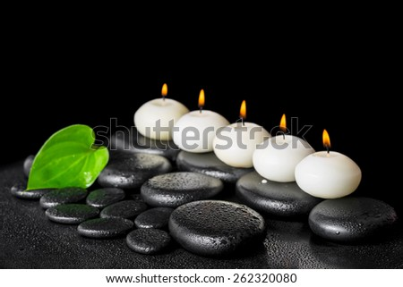 spa still life of row white candles and green leaf on black zen stones background with drops - stock photo