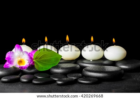 spa still life of row white candles, orchid flower dendrobium and green leaf on black zen stones background with dew - stock photo