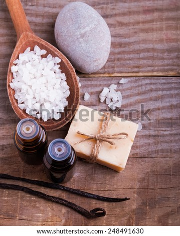 Spa still life on the wooden background, top view. Hand made soap, vanilla pods, aroma oils and sea salt.
