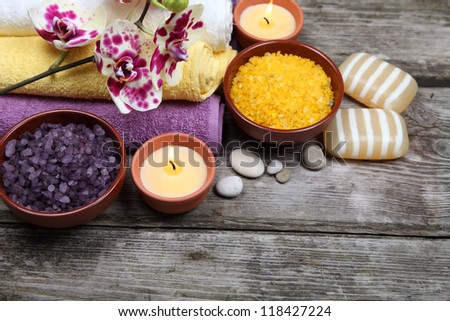Spa still life: soap, salt for baths, a flower and towels on a wooden background - stock photo