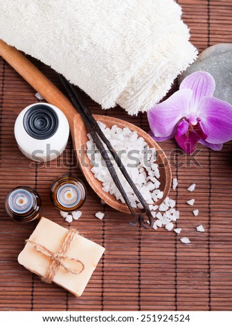 Spa still life with aroma oils, sea salt and vanilla pods. Top view. - stock photo