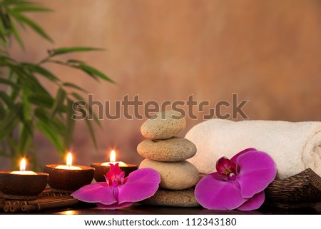 Spa still life with aromatic candles,towel and stack of zen stones. - stock photo