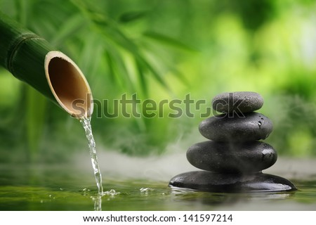 Spa still life with bamboo fountain and zen stone - stock photo