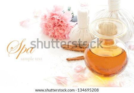 Spa still life with bottle of aromatic essence oil, herbal massage ball and carnation flower. - stock photo