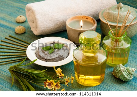Spa still life with Bottle of aromatic essence oil, organic scrub, bottle of fragrance reeds diffuser  orchid flower, towel, candle, incense and shells. - stock photo