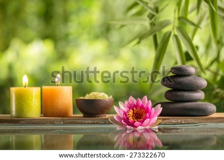 Spa still life with burning candles,zen stone and salt reflected in a serenity pool - stock photo