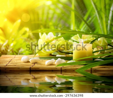 Spa still life with candle,pebble stones and orchid on bamboo mat - stock photo