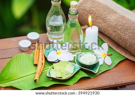 Spa still life with frangipani, towel, candles, fresh aloe and green leaf - stock photo