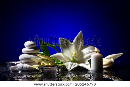 spa still life with freshness white lily, stack of several stones and  burning candles on  black bright table with water drop,  blue light and dark background - stock photo
