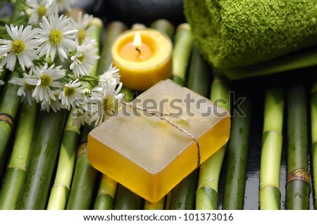 Spa still life with green towels, salt on spoon, orchid, candle