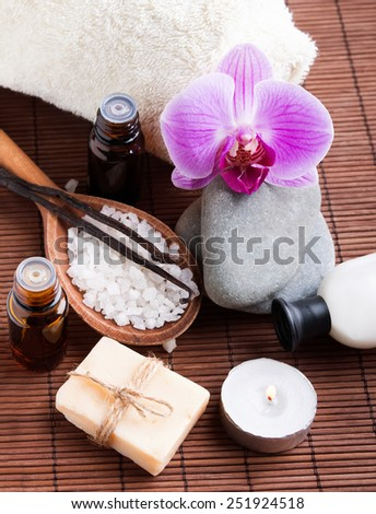 Spa still life with hand made soap, sea salt, vanilla pods and pink orchid.