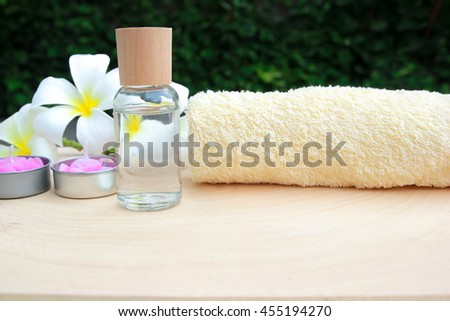 Spa still life with oil, towel, flower, aromatic candles on wooden table - stock photo