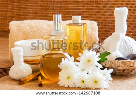 Spa still life with Oil treatment, herbal massage balls, exfoliation salt scrub and spa accessories. - stock photo