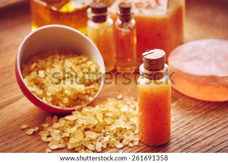 Spa still life with orange scrub for body on wooden background - stock photo