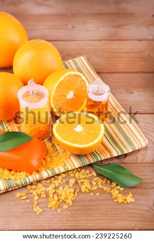 Spa still life with oranges, bottles of bath salt and oil, and bar of soap on striped napkin on wooden background - stock photo