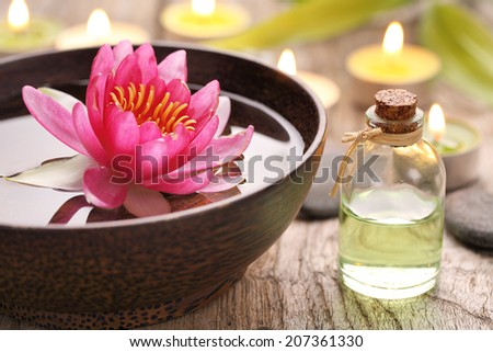 Spa still life with perfume bottle and lotus flower - stock photo