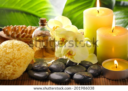 Spa still life with sponge,zen stone and burning candles. - stock photo