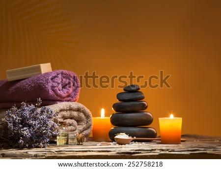 Spa still-life with stacked of stone and burning candles, close-up. - stock photo
