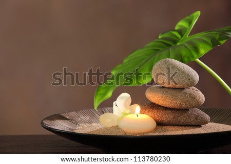 Spa still life with stacked of stone,burning candle and dishgyi leaf. - stock photo