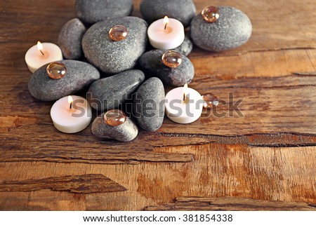 Spa still life with stones and candlelight on wooden background - stock photo