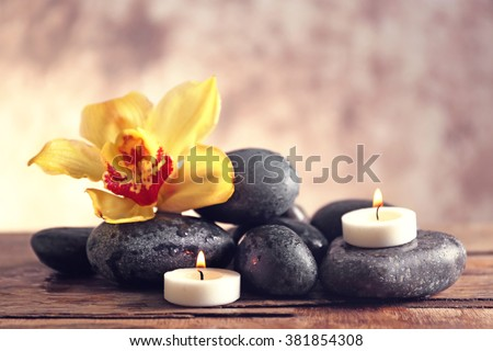 Spa still life with stones, flower and candlelight on blurred pastel background - stock photo