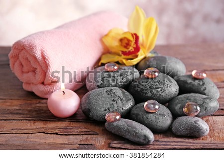 Spa still life with stones, towel, flower and candlelight on wooden background - stock photo