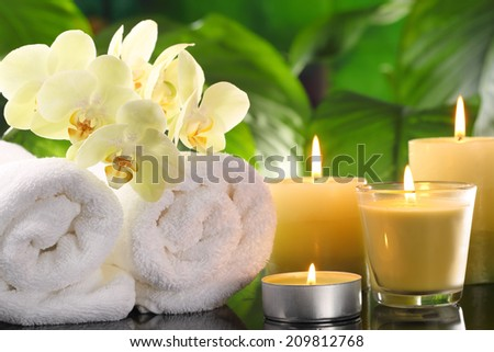 Spa still life with towel and burning candles. - stock photo