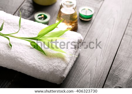 SPA still life with towel, candles and bamboo leaves on a black wooden surface - stock photo
