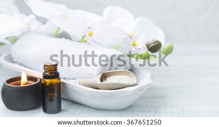 Spa still life with towel,white orchid,sea salt,bath oil and candle  - stock photo