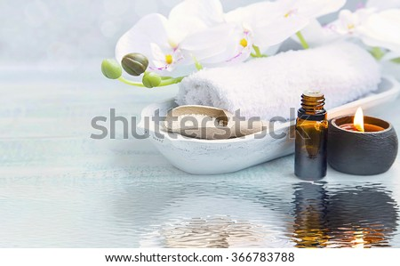 Spa still life with towel,white orchid,sea salt,bath oil and candle on water reflection - stock photo