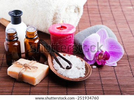 Spa still life with vanilla pods, hand made soap, aroma oils and pink orchid flower - stock photo