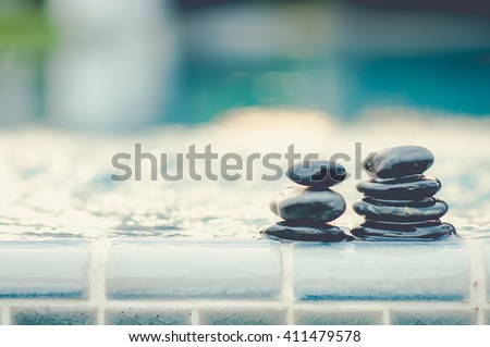 Spa still life with water lily and zen stone in a serenity pool  - stock photo
