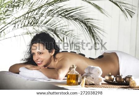 Spa Stone Massage. Beautiful Woman Getting Spa Hot Stones Massage in Spa Salon. - stock photo