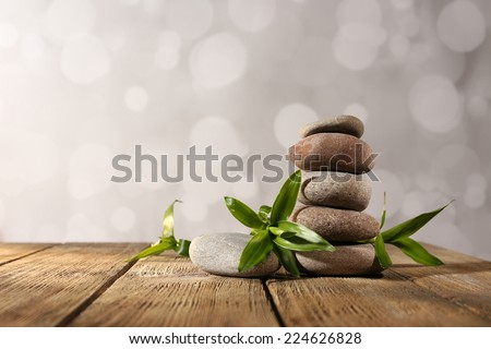 Spa stones and bamboo on wooden table on light background - stock photo