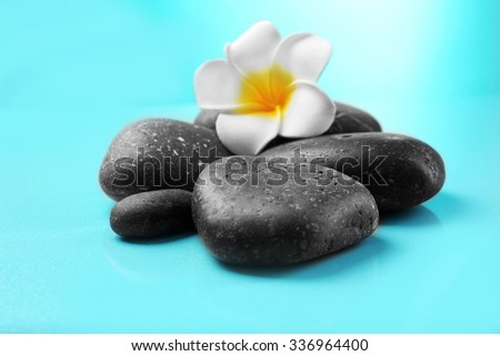 Spa stones and flower on blue background - stock photo
