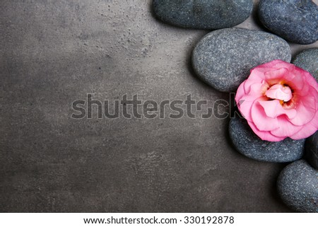 Spa stones and flowers on grey background - stock photo