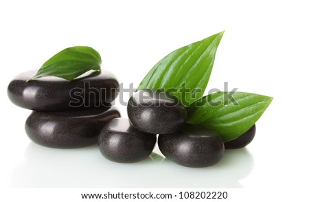 Spa stones and green leaves isolated on white - stock photo