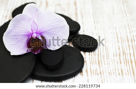Spa stones and  orchid flower heads on a old  wooden  background - stock photo